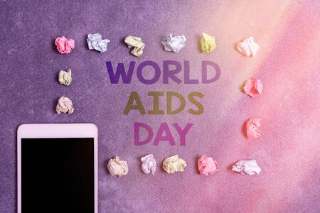 Writing note showing World Aids Day. Business concept for an international day to raised awareness of the AIDS pandemic Paper accessories with smartphone arranged on different background