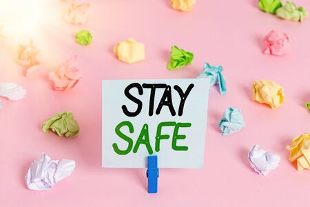 Word writing text Stay Safe. Business photo showcasing secure from threat of danger, harm or place to keep articles Colored crumpled papers empty reminder pink floor background clothespin
