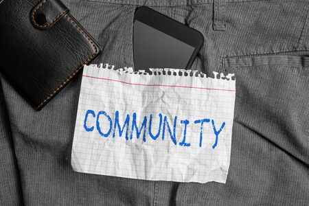 Word writing text Community. Business photo showcasing group of showing with a common characteristics living together Smartphone device inside trousers front pocket with wallet and note paper