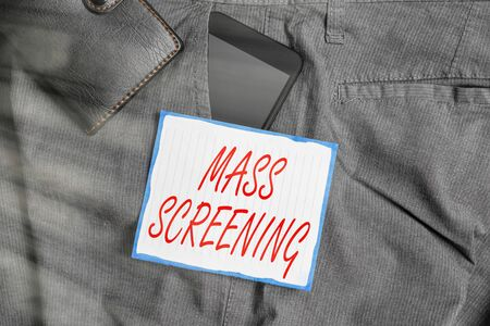 Text sign showing Mass Screening. Business photo showcasing health evaluation performed at a large amount of population Smartphone device inside trousers front pocket with wallet and note paper 스톡 콘텐츠