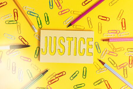 Conceptual hand writing showing Justice. Concept meaning use of power as appointed by law standards to support fair treatment Flat lay above empty paper with pencils and paper clips