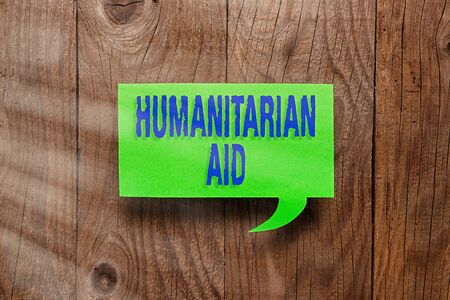 Conceptual hand writing showing Humanitarian Aid. Concept meaning immediate assistance provided after natural and manmade disaster Paper accessories with smartphone on different background