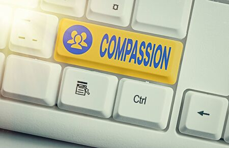 Conceptual hand writing showing Compassion. Concept meaning empathy and concern for the pain or misfortune of others White pc keyboard with empty note paper above white key copy space 版權商用圖片
