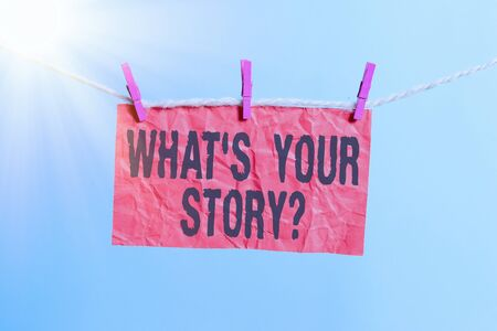 Handwriting text writing What S Your Story Question. Conceptual photo Share or tell us your life experiences and success Clothesline clothespin rectangle shaped paper reminder white wood desk