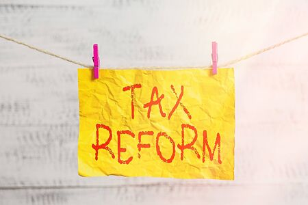 Word writing text Tax Reform. Business photo showcasing government policy about the collection of taxes with business owners Clothesline clothespin rectangle shaped paper reminder white wood desk