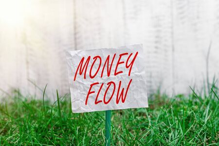 Conceptual hand writing showing Money Flow. Concept meaning it is an indicator of positive or negative in a current day Plain paper attached to stick and placed in the grassy land