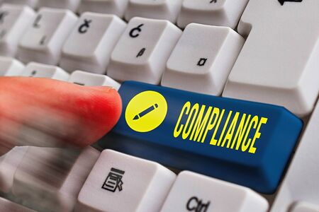 Writing note showing Compliance. Business concept for the action or fact of complying with a wish or commands White pc keyboard with empty note paper above white key copy space