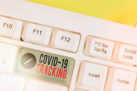 Text sign showing Covid 19 Tracking. Business photo text Distinguishing process of the possible infected individuals White pc keyboard with empty note paper above white key copy space