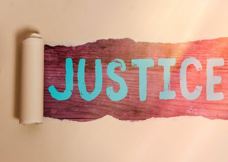 Handwriting text writing Justice. Conceptual photo use of power as appointed by law standards to support fair treatment Rolled ripped torn cardboard placed above a wooden classic table backdrop