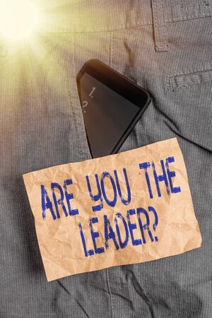 Writing note showing Are You The Leader Question. Business concept for asking for the qualification of being a good boss Smartphone device inside trousers front pocket note paper Foto de archivo - 150365141