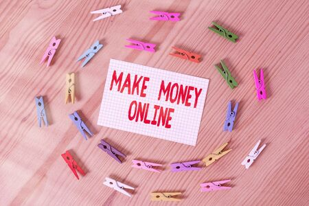 Text sign showing Make Money Online. Business photo text Get paid earn cash through freelancing and web marketing Colored clothespin papers empty reminder wooden floor background office