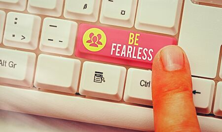 Word writing text Be Fearless. Business photo showcasing act of striving to lead an extraordinary life and make a difference White pc keyboard with empty note paper above white key copy space