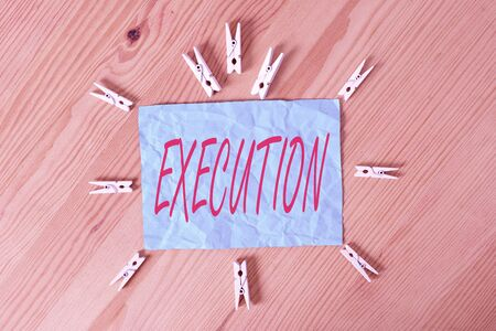 Word writing text Execution. Business photo showcasing it executes or imposes a program order or course of action Colored clothespin papers empty reminder wooden floor background office 스톡 콘텐츠 - 150355051