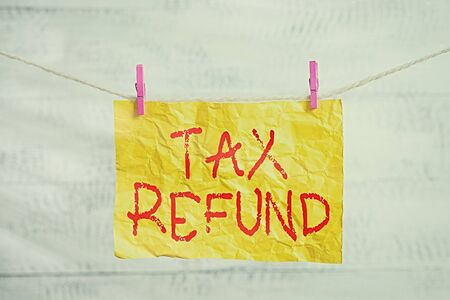 Word writing text Tax Refund. Business photo showcasing excess payment of paid taxes returned to business owners Clothesline clothespin rectangle shaped paper reminder white wood desk 写真素材