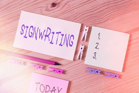 Word writing text Signwriting. Business photo showcasing any type of clear lettering intended for use on symbols Colored clothespin papers empty reminder wooden floor background office