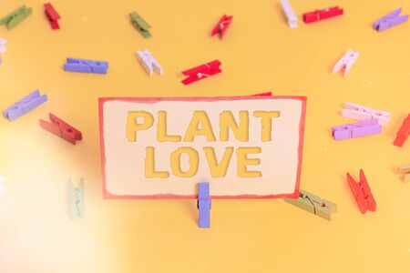 Conceptual hand writing showing Plant Love. Concept meaning a symbol of emotional love, care and support showed to others Colored clothespin papers empty reminder yellow floor office