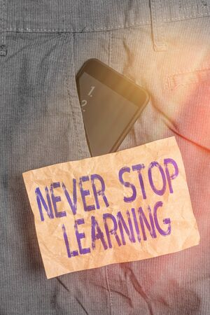 Writing note showing Never Stop Learning. Business concept for continuous education and techniques to be competitive Smartphone device inside trousers front pocket note paper