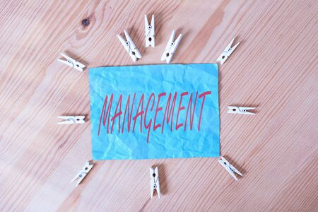 Word writing text Management. Business photo showcasing the authoritative act of directing or controlling things Colored clothespin papers empty reminder wooden floor background office Foto de archivo - 150366793
