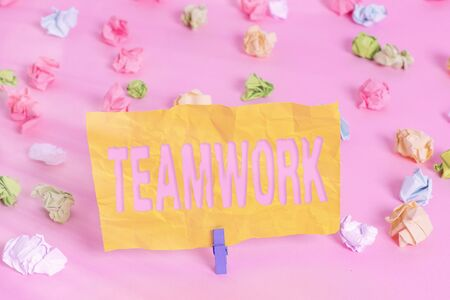 Handwriting text writing Teamwork. Conceptual photo the group s is collaborative effort to accomplish a common goal Colored crumpled papers empty reminder pink floor background clothespin