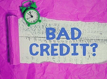 Writing note showing Bad Credit Question. Business concept for a bad credit score due to nonpayment of loans Rolled ripped torn cardboard above a wooden classic table Stok Fotoğraf