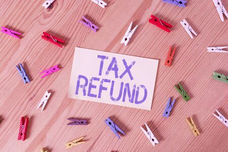 Handwriting text Tax Refund. Conceptual photo excess payment of paid taxes returned to business owners Colored clothespin papers empty reminder wooden floor background office
