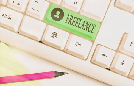 Word writing text Freelance. Business photo showcasing working at different firms rather than being permanently White pc keyboard with empty note paper above white key copy space