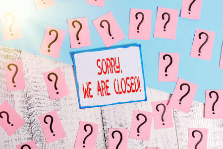 Writing note showing Sorry, We Are Closed. Business concept for apologize for shutting off business for specific time Scribbled and crumbling papers with thick cardboard above wooden table 版權商用圖片