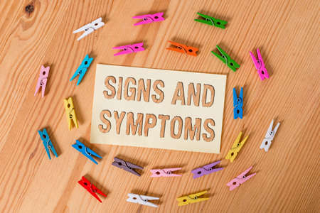 Text sign showing Signs And Symptoms. Business photo showcasing abnormalities that indicate a likely medical condition Colored clothespin papers empty reminder wooden floor background office