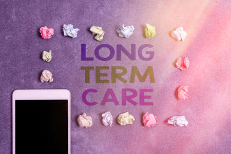 Writing note showing Long Term Care. Business concept for assistance with the basic an individualal tasks of everyday life Paper accessories with smartphone arranged on different background Banque d'images