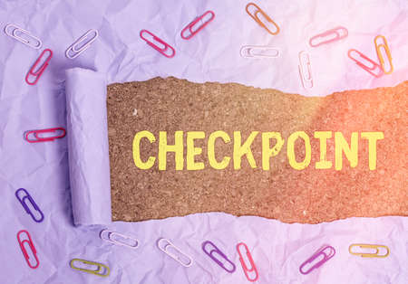 Conceptual hand writing showing Checkpoint. Concept meaning manned entrance, where travelers are subject to security checks Rolled ripped torn cardboard above a wooden classic table