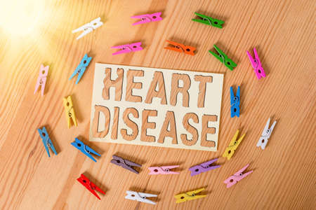 Text sign showing Heart Disease. Business photo showcasing A type of disease that affects the heart or blood vessels Colored clothespin papers empty reminder wooden floor background office
