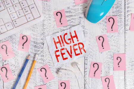 Text sign showing High Fever. Business photo text medical condition which the body temperature higher than usual Writing tools, computer stuff and scribbled paper on top of wooden table