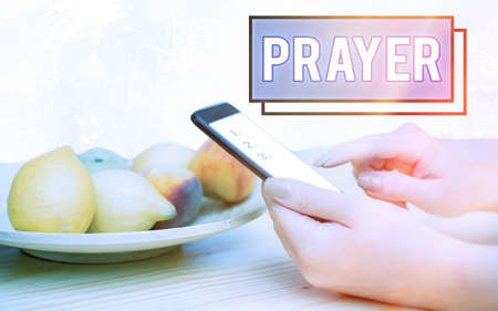Conceptual hand writing showing Prayer. Concept meaning solemn request for help or expression of thanks addressed to God Modern gadgets white screen under colorful bokeh background