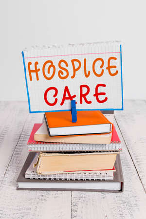 Text sign showing Hospice Care. Business photo text focuses on the palliation of a terminally ill patient s is pain pile stacked books notebook pin clothespin colored reminder white wooden Reklamní fotografie
