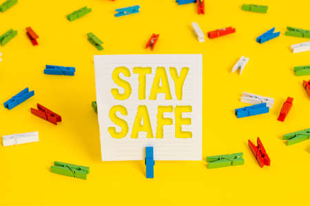 Conceptual hand writing showing Stay Safe. Concept meaning secure from threat of danger, harm or place to keep articles Colored clothespin papers empty reminder yellow floor office Imagens