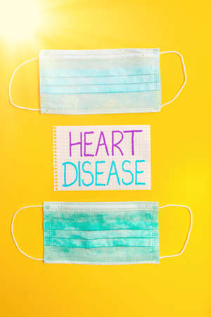 Conceptual hand writing showing Heart Disease. Concept meaning A type of disease that affects the heart or blood vessels Set of medical equipment with notepad for health assessment Reklamní fotografie