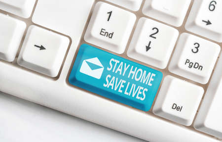 Conceptual hand writing showing Stay Home Save Lives. Concept meaning lessen the number of infected patients by not leaving the house White pc keyboard with empty note paper above white key copy space