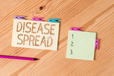 Writing note showing Disease Spread. Business concept for Direct transfer of a viral agent through an individualtoan individual contact Colored clothespin papers empty reminder wooden floor background office Zdjęcie Seryjne