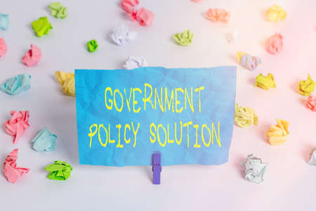 Conceptual hand writing showing Government Policy Solution. Concept meaning designed game plan created in response to emergency disaster Colored crumpled paper empty reminder white floor clothespin