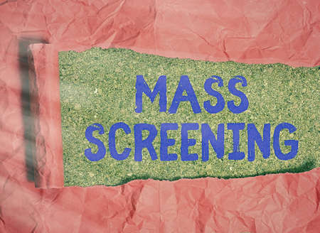 Conceptual hand writing showing Mass Screening. Concept meaning health evaluation performed at a large amount of population Rolled ripped torn cardboard above a wooden classic table