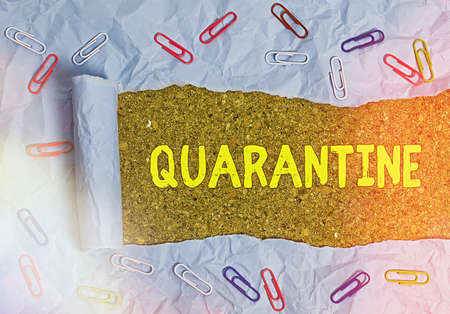 Conceptual hand writing showing Quarantine. Concept meaning restraint upon the activities of an individual or the transport of goods Rolled ripped torn cardboard above a wooden classic table