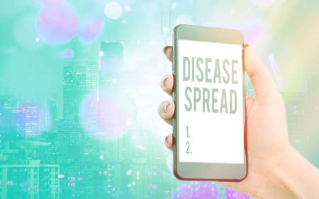 Writing note showing Disease Spread. Business concept for Direct transfer of a viral agent through an individualtoan individual contact Modern gadgets white screen under colorful bokeh background