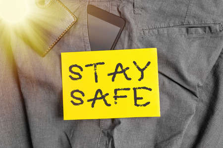 Word writing text Stay Safe. Business photo showcasing secure from threat of danger, harm or place to keep articles Smartphone device inside trousers front pocket with wallet and note paper