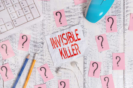 Text sign showing Invisible Killer. Business photo text presence into the air of a substance which are harmful Writing tools, computer stuff and scribbled paper on top of wooden table