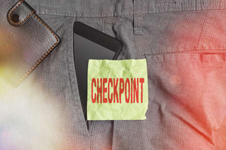 Handwriting text writing Checkpoint. Conceptual photo manned entrance, where travelers are subject to security checks Smartphone device inside trousers front pocket with wallet and note paper