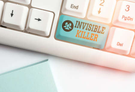 Handwriting text writing Invisible Killer. Conceptual photo presence into the air of a substance which are harmful White pc keyboard with empty note paper above white key copy space Standard-Bild
