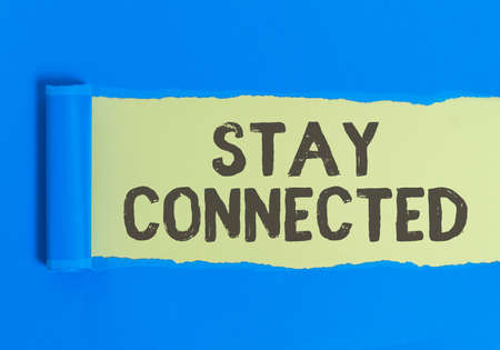 Text sign showing Stay Connected. Business photo text to remain having social professional commercial relationship Rolled ripped torn cardboard placed above a wooden classic table backdrop Banque d'images