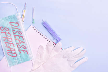Conceptual hand writing showing Disease Spread. Concept meaning Direct transfer of a viral agent through an individualtoan individual contact Set of medical equipment with notepad for health assessment