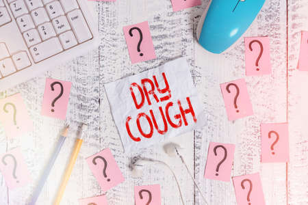 Text sign showing Dry Cough. Business photo text cough that are not accompanied by phlegm production or mucus Writing tools, computer stuff and scribbled paper on top of wooden table Stok Fotoğraf