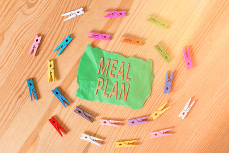 Word writing text Meal Plan. Business photo showcasing act of taking time to plan any number of meals for the week Colored clothespin papers empty reminder wooden floor background office Stok Fotoğraf
